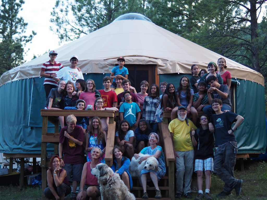 Group picture of campers and staff in front of yurt