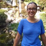 Anastacia, wearing a blue shirt, in front of a small waterfall and trees