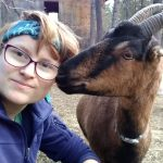 Sky, who has a turquoise bandanna and purple jacket, and is face to face with a largish brown goat