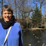 Heather, wearing periwinkle jacket, in front of a pond and trees
