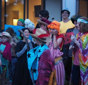ten MFC campers and staff in colorful costumes, hats, scarves, wings etc prepping for the fantasy night program
