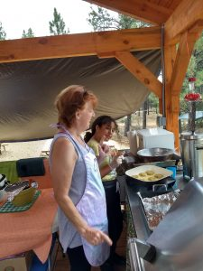 Camp cook and camper helper making falafel in the outdoor camp kitchen