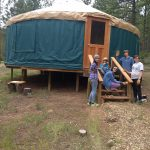 Small group of MFC campers and staff on the porch of a yurt, looking towards the camera