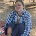 Adriana, seated outdoors at a picnic table, wearing blue flannel, smiling sweetly