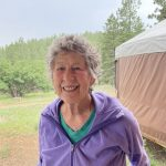Mary Gray, in purple, smiling in front of a yurt
