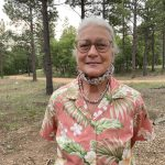 Toni, in pink floral shirt, smiling with mask around chin in front of trees